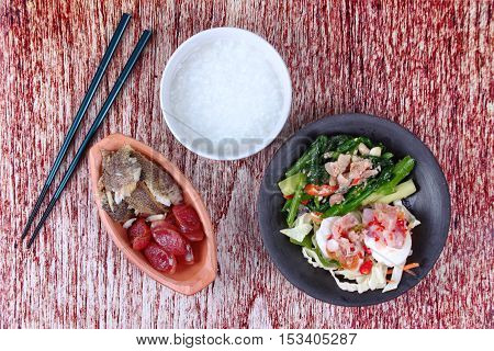 Rice gruel and  side dish as shredded of fried sun-dried fish ,Chinese sausage,spicy salted egg salad and fried kale with salted fish.