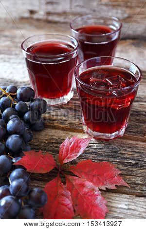 Glasses of grape juice black grapes and autumn leaves