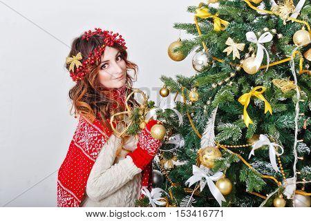 Cute girl decorates the Christmas tree balls. The festive mood.
