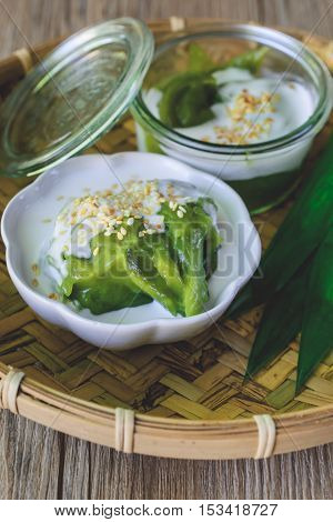 Delicious Thai Dessert Coconut sweet pudding with coconut milk topping on Threshing Basket