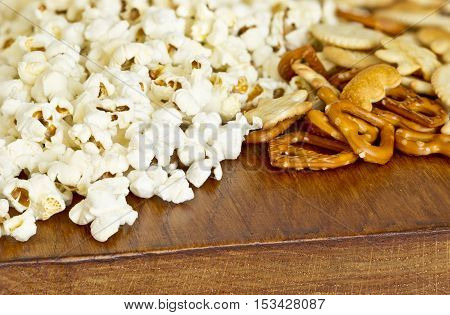 ready to eat popcorn and pretzel snacks spread out on a wooden board