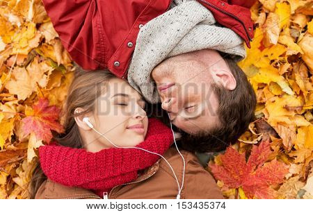 love, relationship, season, family and people concept - close up of happy couple with earphones listening to music and lying on autumn leaves