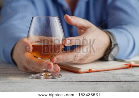 Relaxation Concept - A Glass Of Brandy In Male Hands. Selective Focus.