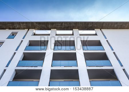 White living house with appartments and blue balconies