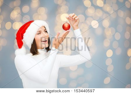winter, people and holidays concept - happy smiling woman in santa helper hat with christmas tree decoration ball over lights background