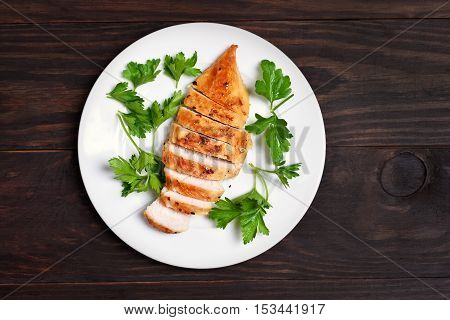 Roasted chicken breast decorated with parsley on white plate over wooden background top view