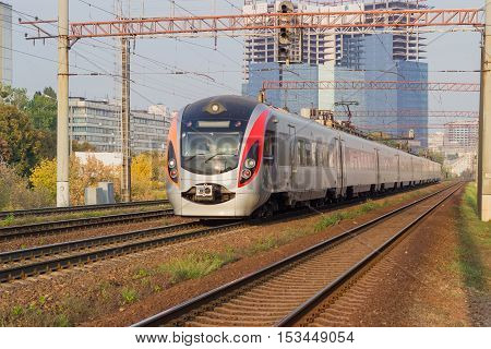 High-speed inter-city train on the background of urban development and construction in autumn day