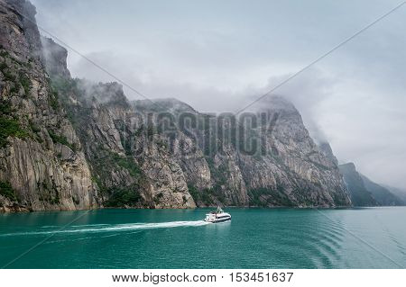 Norwegian Lysefjord view with small ferry on the scenic landscape of the fjord. Scandinavia, Norway.
