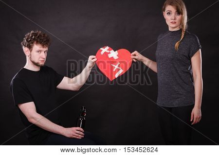 Unhappy couple. Family and alcoholism problems. Addiction and trouble of drinking. Man with alcohol bottle. Sad woman holds paper broken heart.