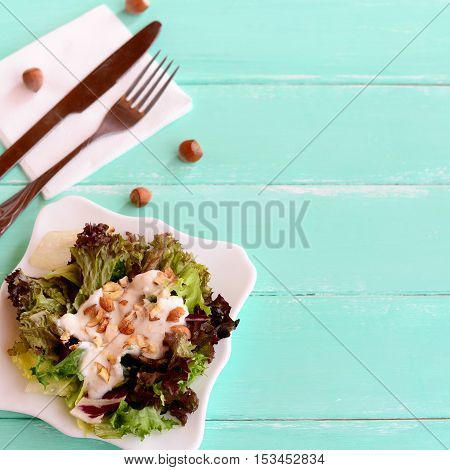Salad leaves mix with yogurt and nuts on a plate. Salad is cooked from radicchio, lettuce, iceberg, frieze leaves. Fork, knife, napkin, raw nuts on a wooden background with empty place for text