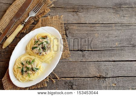 Pasta with champignons, cheese and dill on a plate, fork, knife on old wooden background with empty copy space for text. Delicious pasta nests with filling. Top view