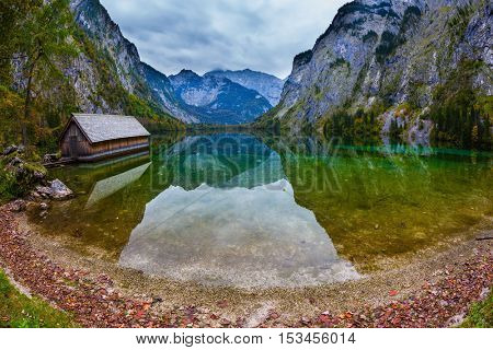 The concept of active tourism and ecotourism. Enchanted Lake Obersee in the Bavarian Alps. Boat garages on the shores