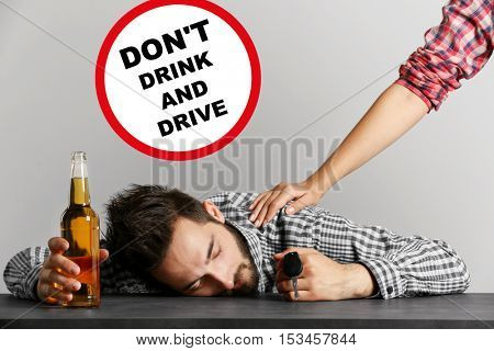 Drunk young man with car key and beer bottle at bar. Sign with text DON'T DRINK AND DRIVE on background.
