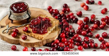 The red berries. Cranberry. Jam from cranberries in a vintage jar. Cookies. Silverware. Spoon. A wooden Board. Light linen tablecloth.