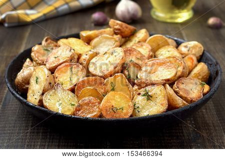 Fried potatoes in a frying pan on wooden table