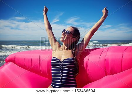 A shot of sincere smiling woman stretching her hands up with palms put in fist. Woman sitting on a deep rosy air rubber boat, wearing blue stripes swimming suit and brown sunglasses
