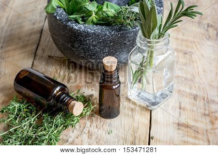 aromatherapy herbal preparation with pounder at wooden background