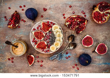 Healthy fall and winter breakfast set. Acai superfoods smoothies bowl with chia seeds pomegranate sliced banana fresh figs and hazelnut butter. Overhead top view.