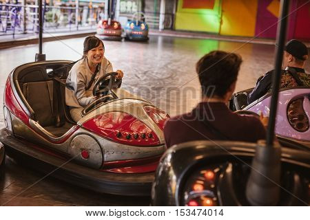 Friends having fun on bumper car ride in amusement park. Young man and woman having fun with bumper cars at fairground.