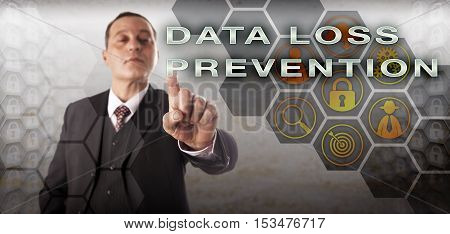 Confident businessman touching DATA LOSS PREVENTION on a control monitor. Information technology concept for data security blocking of sensitive data and detection of potential data breaches.