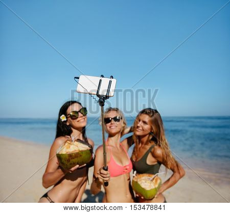 Three young women in bikini on the beach taking self portrait with smart phone on selfie stick. Group of female friends holding coconuts and taking selfie.