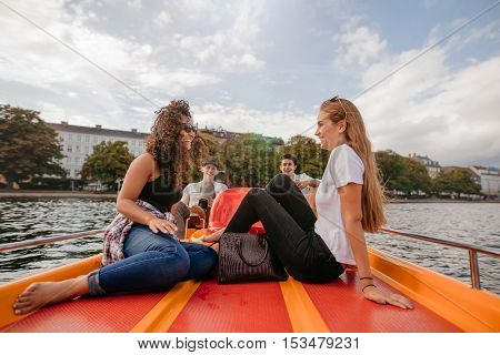 Shot of teenage girls sitting in the front of a boat in lake with male friends pedaling in background. Teenage friends relaxing on pedal boat in lake.