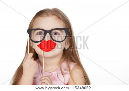 Little girl in hiding her face after fake glasses and paper lips. Isolated on white background