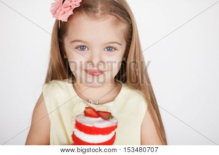 Little girl celebrating her birthday. Closeup cute child girl holding a red velvet mini cake with strawberry on white background