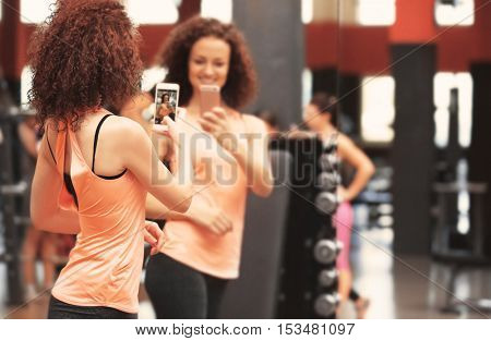 Young sportive woman taking selfie near mirror in gym