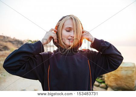 Young pretty sports woman in hoodie resting after training on beach