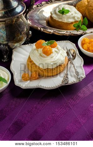 Cream cakes. Yellow cloudberries. Mint leaves. The desserts on the plate. Still life with vintage kitchenware. Purple background. Silverware.