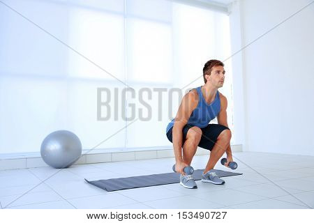 Young man doing exercises with dumb-bells on rug indoor