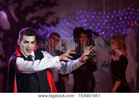 Young man in vampire costume at Halloween party