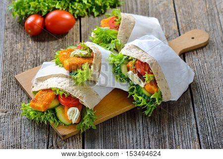 Pita sandwich stuffed with crispy fish fingers, fresh salad and remoulade sauce