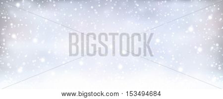 Soft and dreamy winter Christmas background with light effects and snow fall in silver blue white shapes for the holiday season to come.
