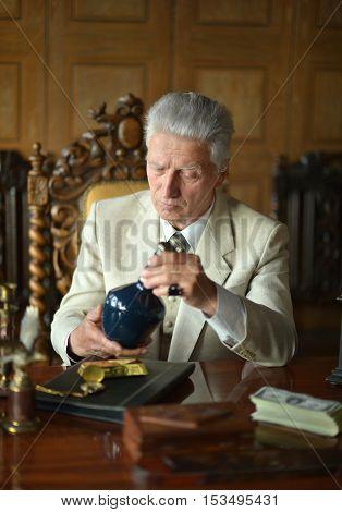 Mature male mafia boss on the table