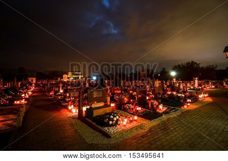 Ljubljana Slovenia - November 1 2012: candles and lantern burning on graves at Cemetery at night for a catholic - christian holiday All Saints' Day. Solemnity of All Saints. All Hallows eve. November 1st. Feast of All Saints. Hallowmas. All Souls' Day.