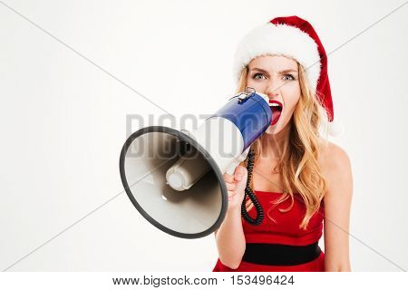 Angry young woman in santa claus costume shouting in megaphone over white background