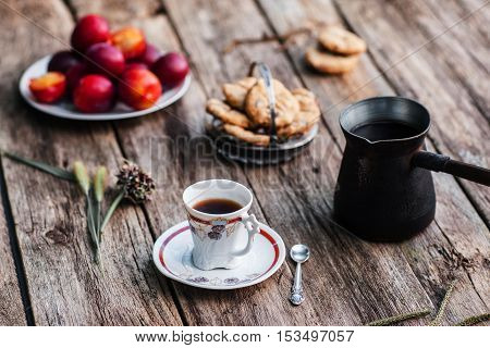 Cup of coffee and pot with different tasty snacks on wood. Ol rustic table served for traditional turkish coffee break with sweet cookies and fresh plums