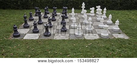 Chessboard and chess pieces on tiles in the garden, playing wooden chess pieces, business teamwork competition games concept, leadership hand of businessman playing chess.