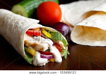 Grilled Chicken And Salad Tortilla Wrap With White Sauce Isolated On Dark Background. Next To Plain