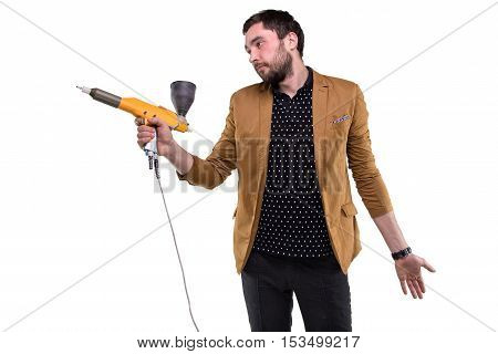 Young brunette man with powder gun on white background