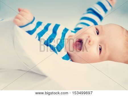 happy little boy lying in the bed. Cute four month old baby in striped sleepsuit at home.