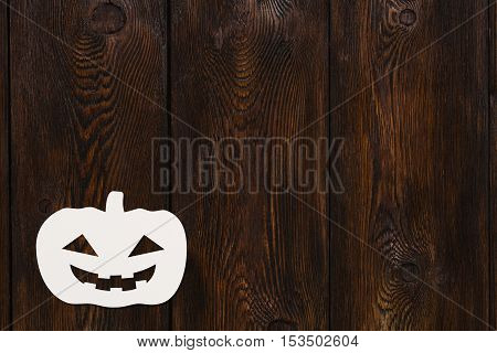 Halloween holiday. Paper smiling Grand Pumpkin. Dark wooden background, copyspace. Abstract conceptual image