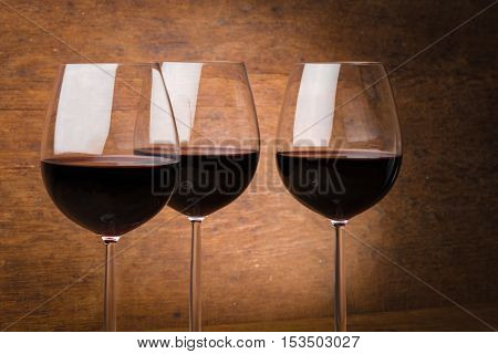 Three fine wine glasses half full with liquid over brown wooden background with spotlight effect