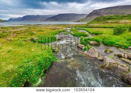 River flows from a waterfall Iceland in summer