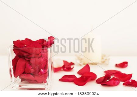 Glass vase filled with red rose petals white aromatic vanilla candle. White background. Aromatherapy concept. Glass vase filled with red rose petals white aromatic vanilla candle. White background. Aromatherapy concept. Romantic background