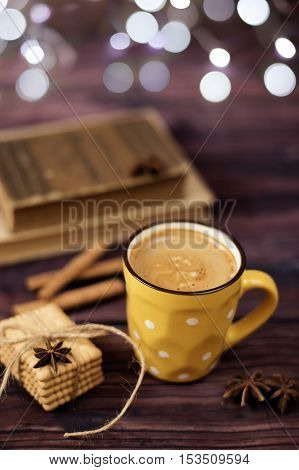 Mug Of Coffee, Cookies, Star Anise, Cinnamon, Old Books. Blurred Lights, Wooden Background. Winter T