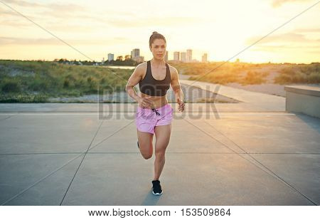 Muscular active woman working out running across a cement forecourt approaching the camera at speed against a distant cityscape at sunrise