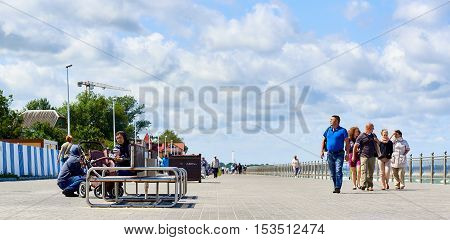 Zelenograd Russia - July 16 2016: People walking along the seafront promenade. Curonian spit Kaliningrad region. Russia